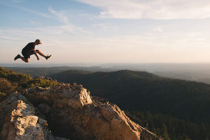 man leaping in mountains